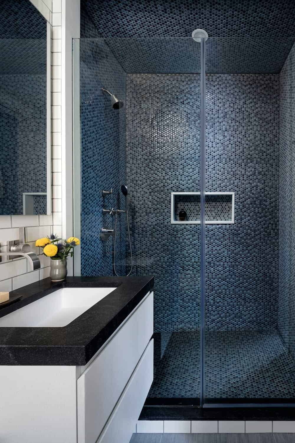 This simple bathroom is elevated with its brilliant black and green patterned tiles of the shower room floor, ceiling and walls that provide a nice background for the shower room fixtures and white vanity that has a black countertop.