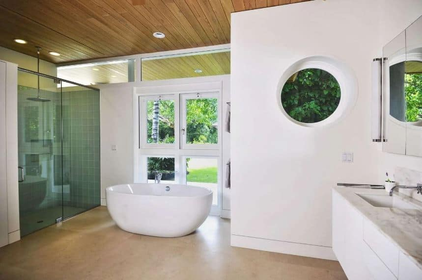The white walls and white freestanding bathtub are sandwiched by the matching beige marble floor tiles and the wooden shiplap ceiling that has recessed lights and showerhead over the shower area enclosed in tinted glass.