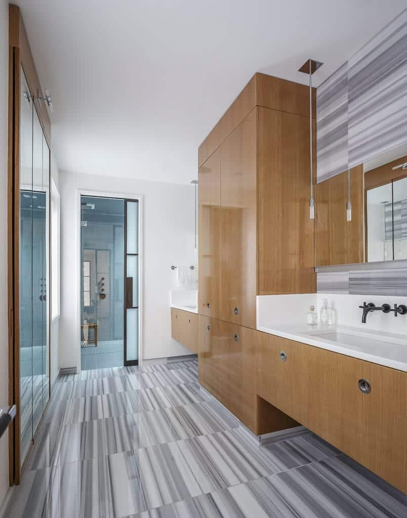 The shower area at the far end of the bathroom is separated from the vanity area with a sliding frosted glass door. This vanity area is dominated by a large wooden structure that houses two sinks as well as cabinets and drawers.