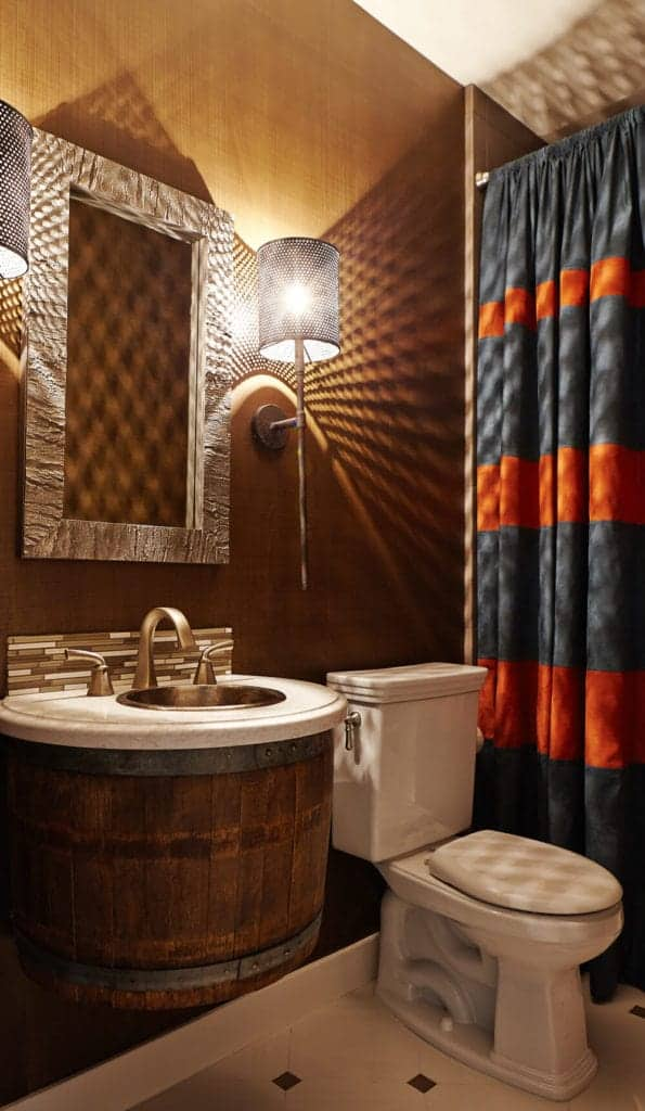 The highlight of this bathroom is the rustic repurposed half of a barrel serving as a circular vanity that matches with the brown wooden wall that makes the white toilet and countertop stand out as well as the white flooring.