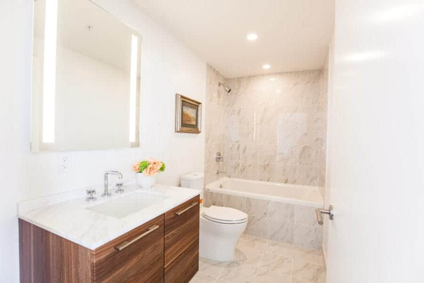 The white walls and ceiling of this simple bathroom is complemented by the beige marble tiles of the flooring that extends to the bathtub inlay and the walls of the shower room that has fixtures matching those of the sink.