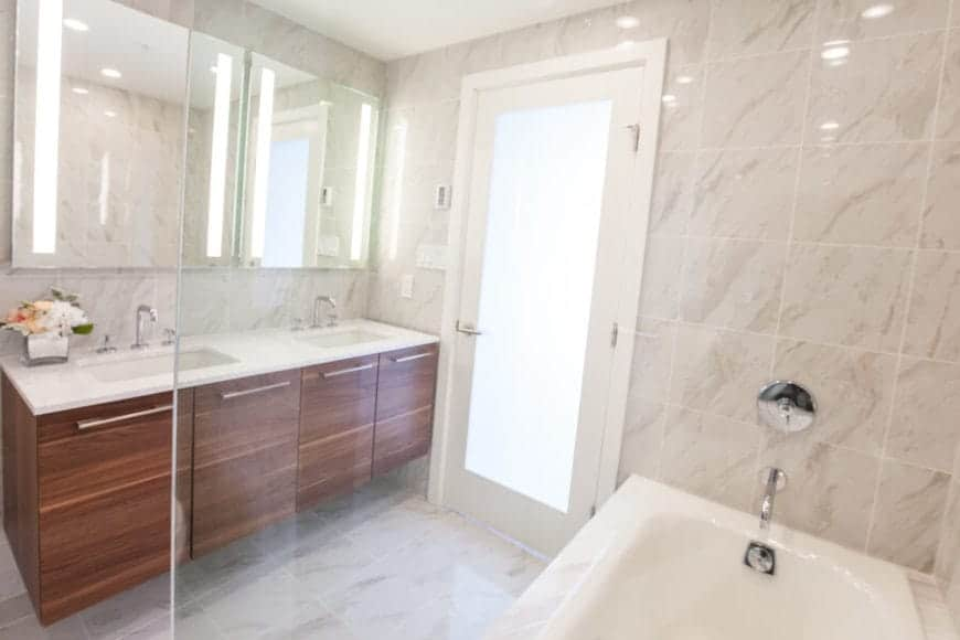 The wooden floating vanity of this primary bathroom has two sinks topped with a couple of large borderless mirrors that match the glass walls of the shower area and bathtub with beige tiles.