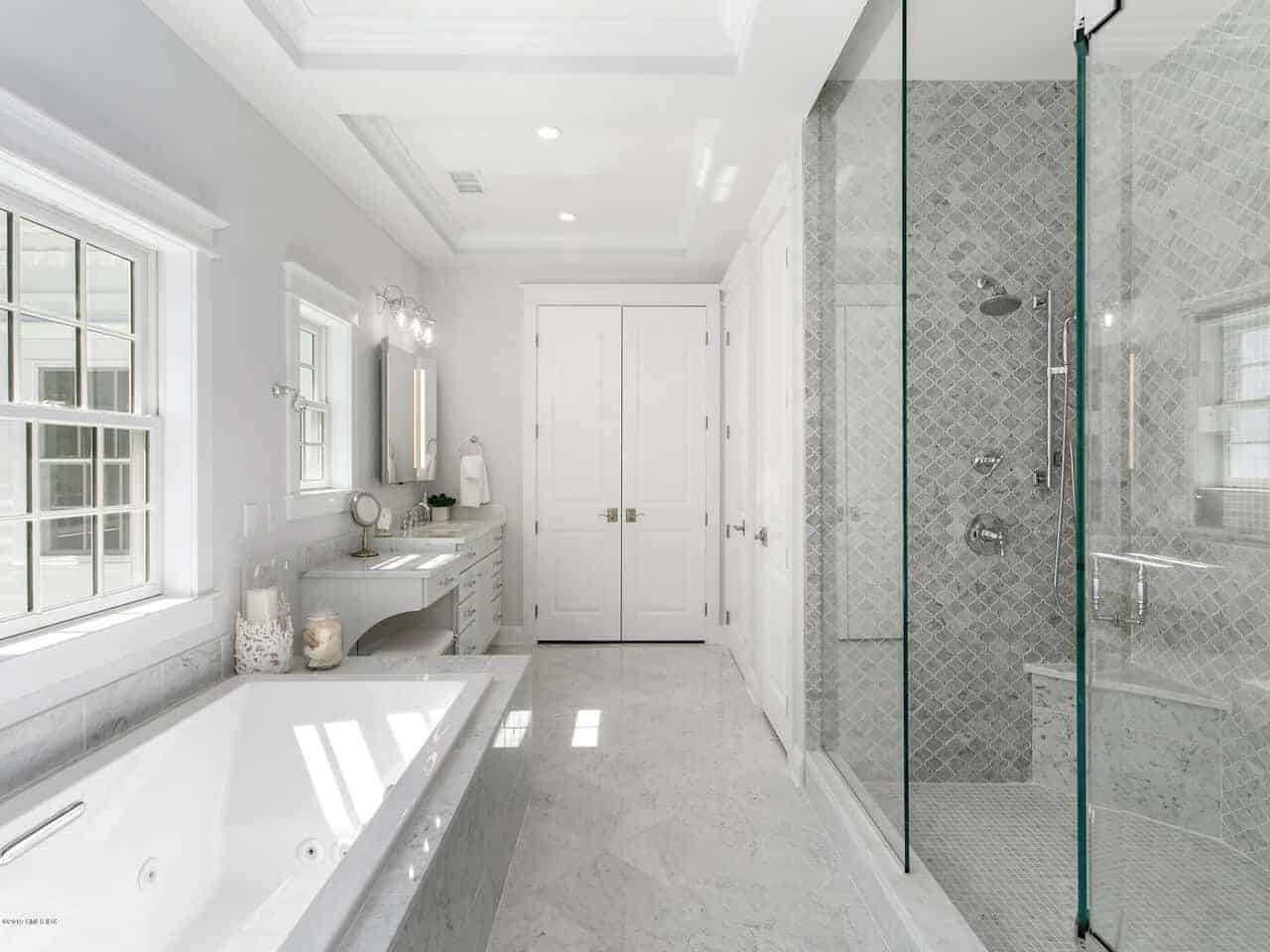 This is a bright and charming primary bathroom that has a hallway in the middle with a white marble flooring that complements the white bathtub across from the shower area that has gray wall tiles and a glass door.