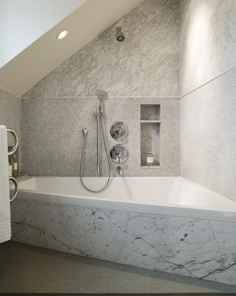 This white corner bathtub is placed in an alcove with a white shed ceiling that has a recessed light illuminating the silver shower fixtures that stand out against the gray marble tiles of the wall and bathtub inlay.