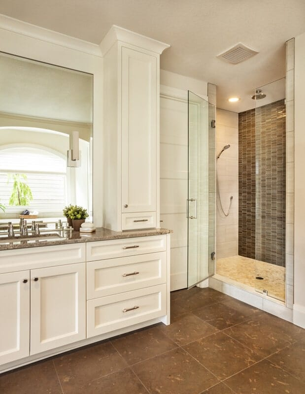 The brown tiles of the flooring is a nice complement to the white wooden structure housing the vanity with a brown marble countertop topped with mirror matching the glass door leading to the shower area.