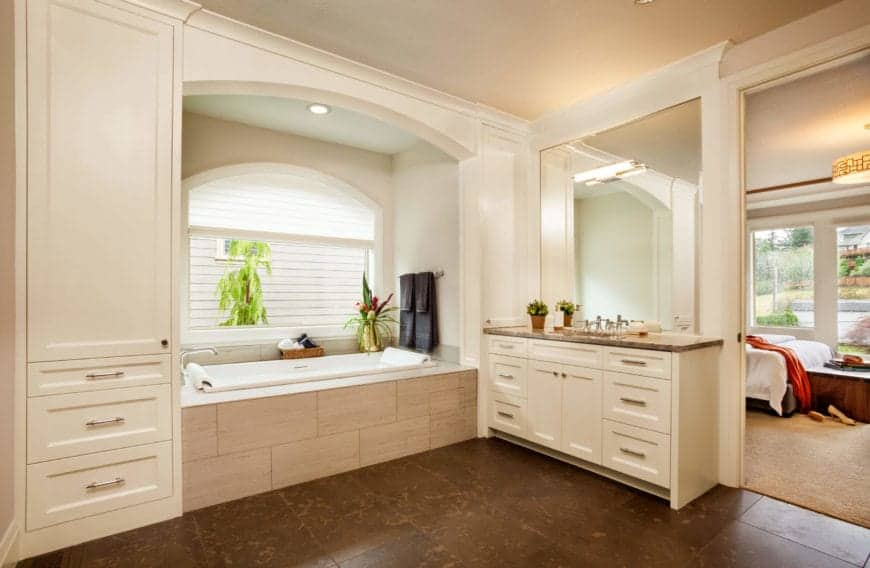 This is an elegant primary bathroom that has a bathtub placed in an alcove of light pink walls and inlay tiles illuminated by the arched window that has white shutters for privacy. This contrasted by the brown flooring tiles that matches the countertop of the vanity beside the bathtub.