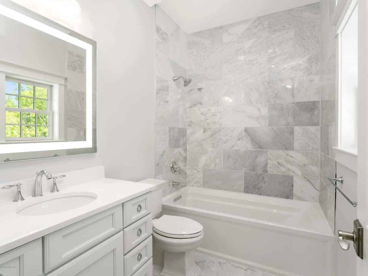 The marble tiles of the shower area walls matches with the flooring. The white toilet is flanked by the bathtub and the white vanity that has a white countertop paired with a vanity mirror with back lights on its frame.