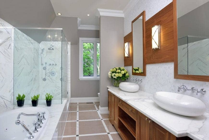 There is a couple of white oval freestanding sinks on the white marble countertop of the vanity that has wooden drawers, cabinets and shelves matching with the frames of the vanity mirrors that also houses the wall-mounted lamps.
