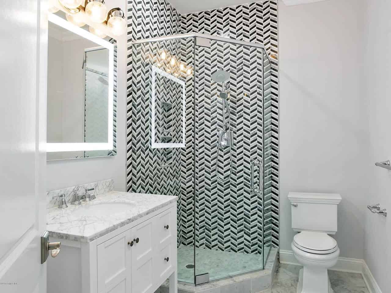 The shower area of this simple bathroom has black and gray wall tiles arranged in a herring bone pattern that gives a nice contrast to the solid white walls that blend with the white toilet and vanity topped with a mirror that has a backlight on its frame.