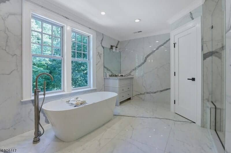 This spacious primary bathroom features a freestanding bathtub placed by a window that shows the lush greenery of the outdoors to provide a nice contrast to the white marble flooring and walls as well as the white ceiling.