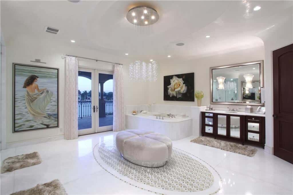 This is a spacious Transitional-Style primary bathroom with white ceiling and walls adorned with framed paintings that augment the elegance of the white floors and silver-trimmed vanity beside the corner bathtub.