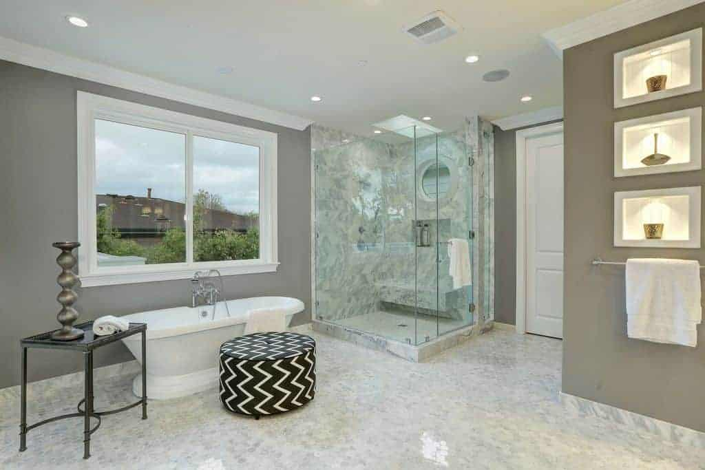 This airy and bright master bathroom has shower area on the corner that is enclosed with tinted glass beside the freestanding bathtub brightened by the white-framed window of the gray wall contrasted by a white marble flooring.