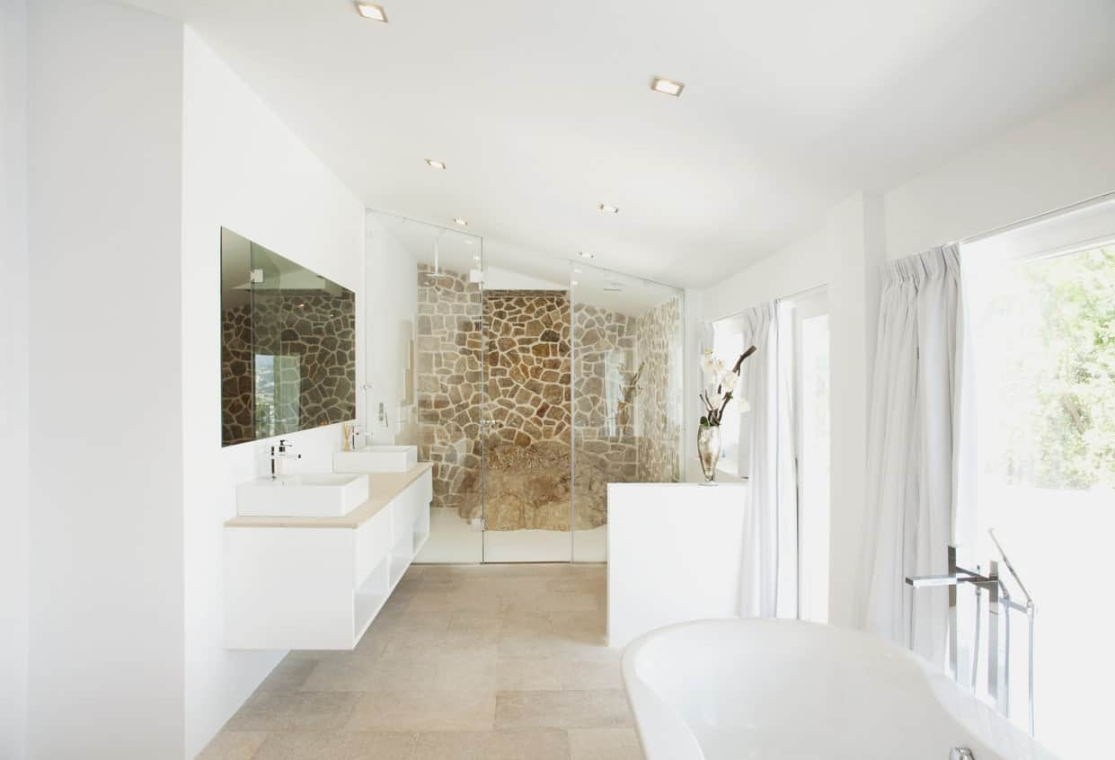 The highlight of this white primary bathroom is the far wall in the shower area that has a brown hue with a unique giraffe pelt pattern that stands out against the white shed ceiling, white tub and white floating sink with a beige countertop matching the flooring.