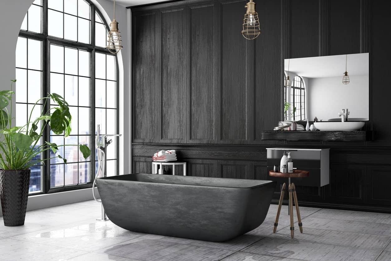 The large floor-to-ceiling window of this spacious bathroom brings in ample natural lights on the black wall of the floating vanity with a white freestanding sink and a mirror. This is paired with the black freestanding bathtub in the middle of the gray flooring.