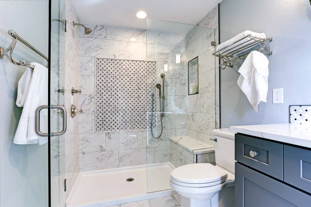 The light gray walls of this intimate bathroom is nicely complemented by the white marble tiles of the shower area that has a glass door beside the toilet and dark gray vanity with white countertop.