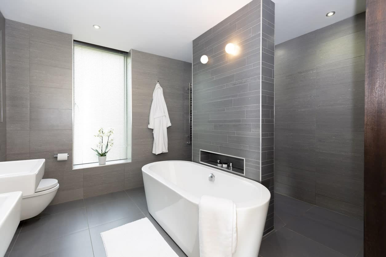 The white soaking tub is separated from the shower area by a wall panel that has a black finish reflecting the dark hues of the flooring and walls that makes the white porcelain tub, toilet and sinks stand out.