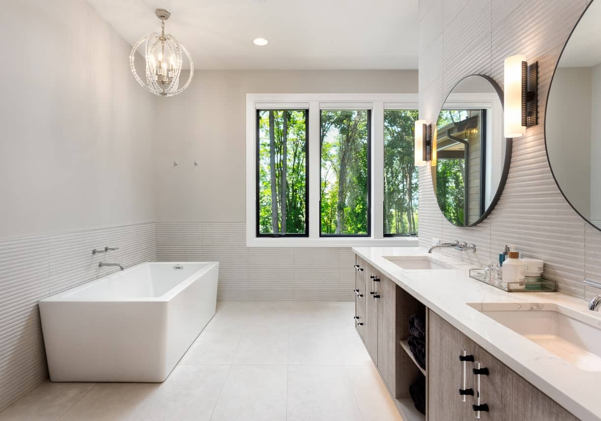 The spherical pendant lighting is a nice accent to the light gray walls that have a subtle texture contrast on the lower half of the walls making the smooth bathtub and vanity countertop stand out.