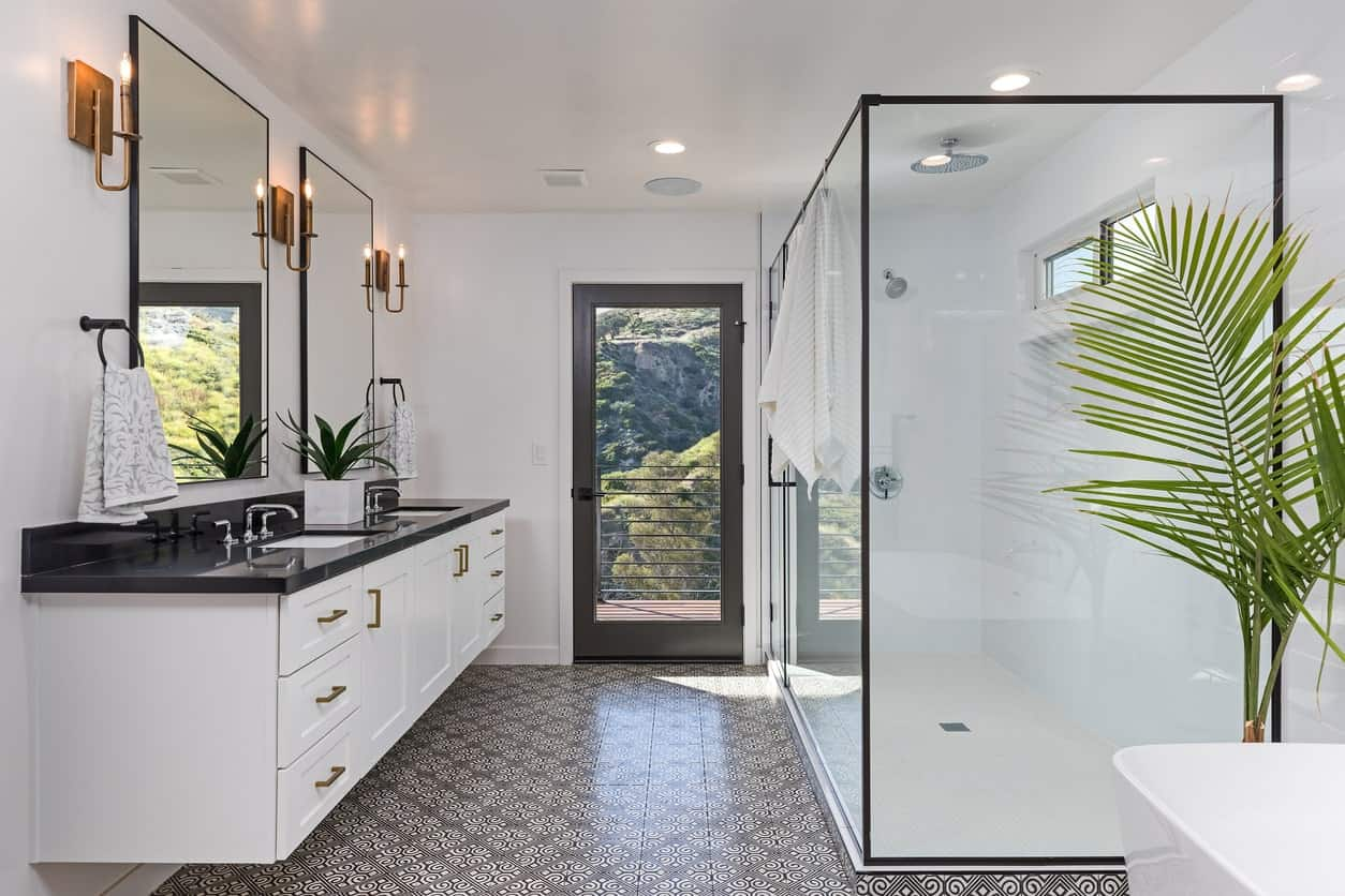 Across from the shower area is the white floating vanity that has two sinks in its black countertop complemented by a pair of vanity mirrors flanked by brass wall-mounted lamps matching the handles of the cabinets and drawers.