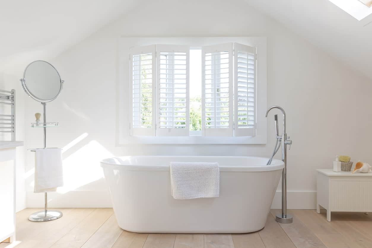 This bright and relaxing master bathroom has a white freestanding bathtub placed by a shuttered window that blends in with the white walls and white cathedral ceiling that has a sky light illuminating the light hardwood flooring.