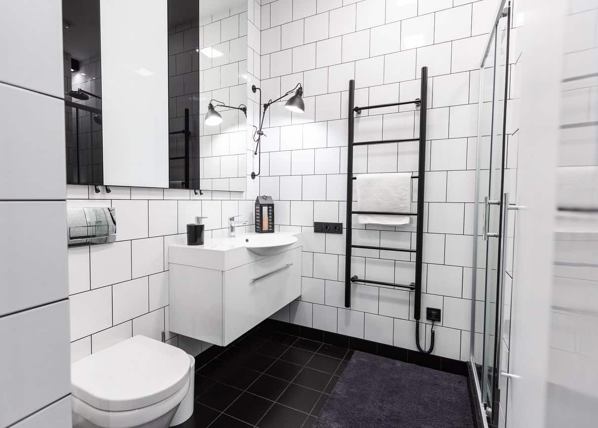 The black tiles of the floor is contrasted by the white tiles of the walls that is fixed with black grout to emphasize the lines and brick wall pattern paired with the white toilet and floating vanity.