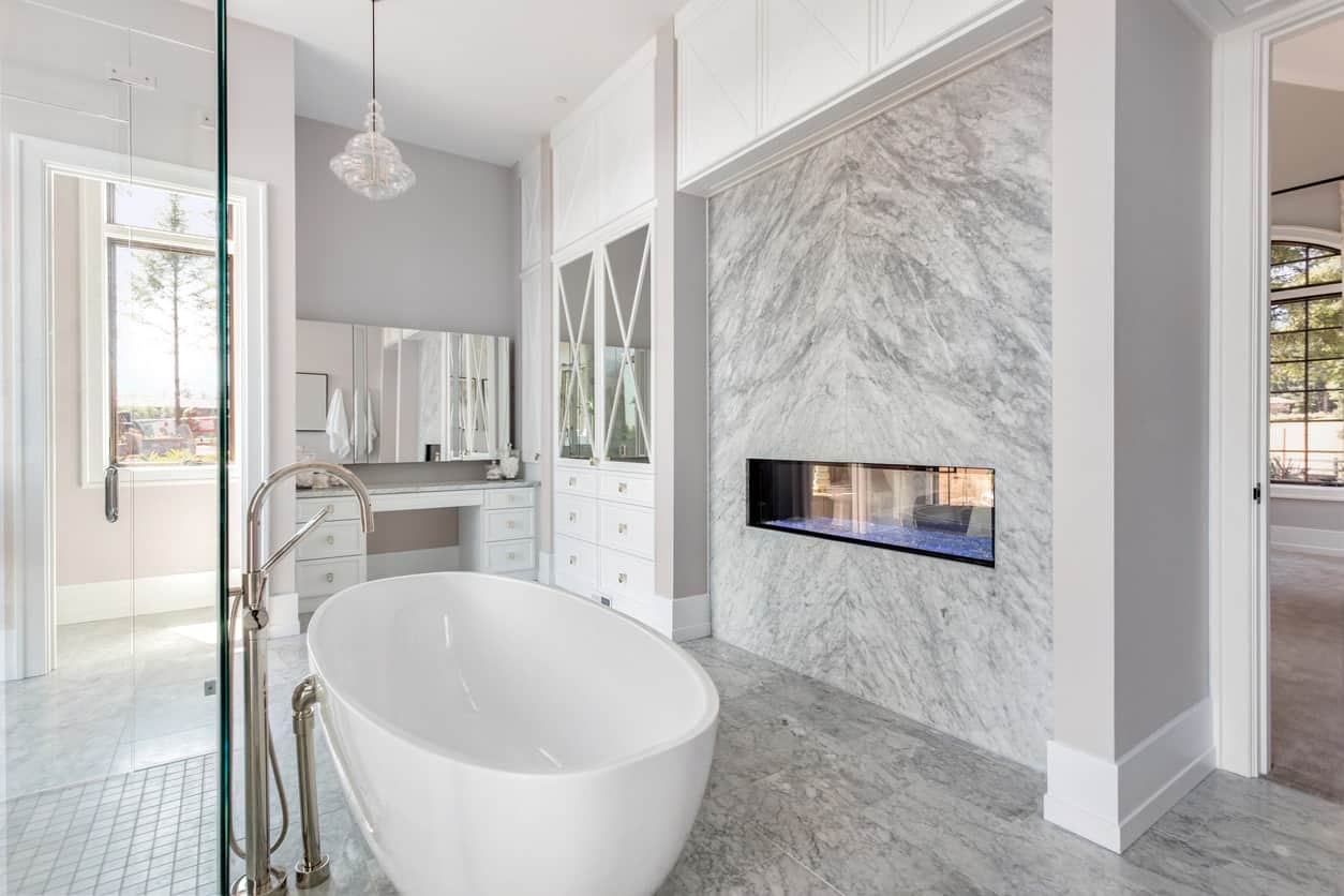 The oval freestanding bathtub is in the middle of the marble flooring that extends to the wall that houses the modern fireplace. This is given a nice background of a vanity area filled with white cabinets and drawers against the gray walls.