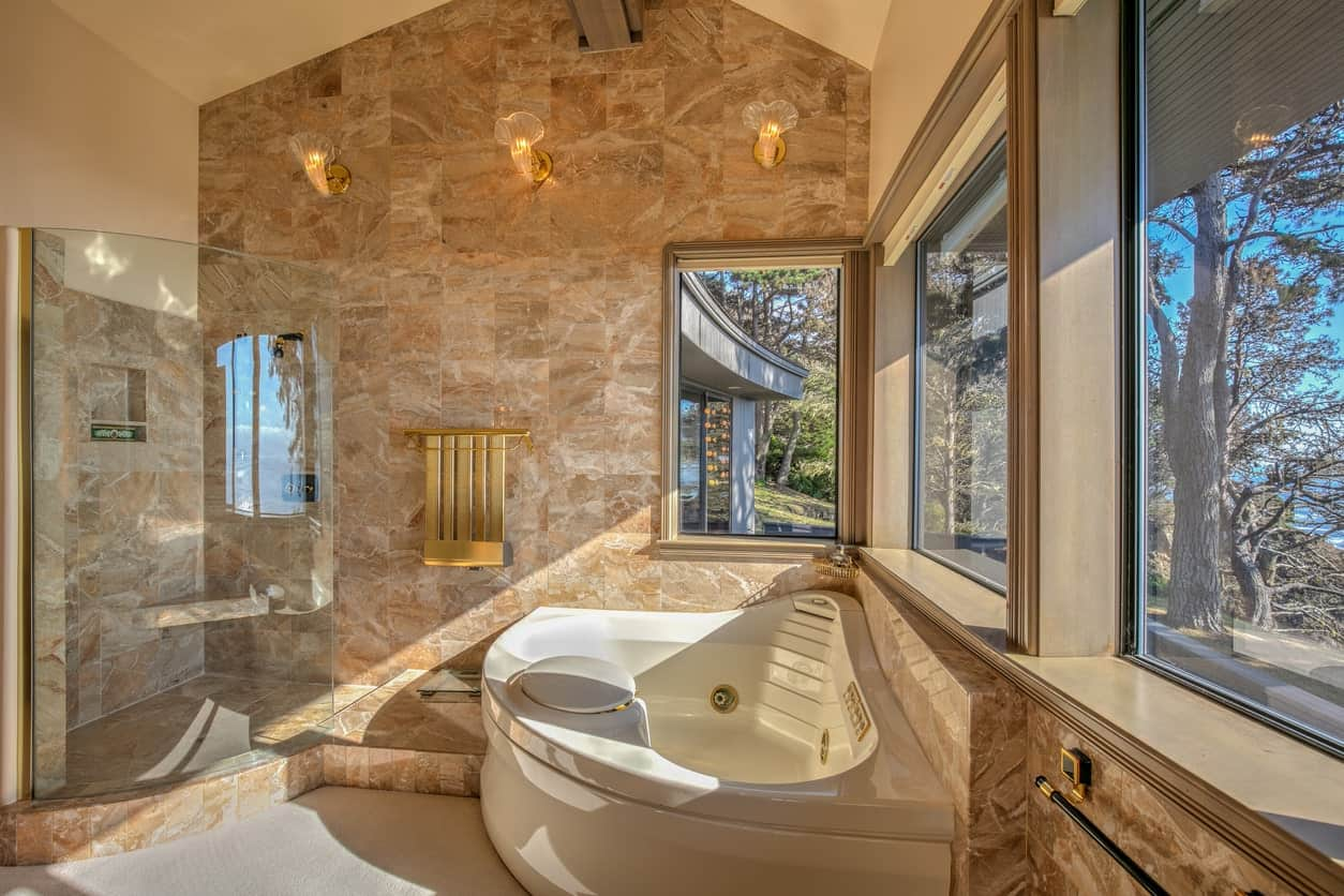 This is a charming and elegant master bathroom with a corner bathtub beside the glass enclosed shower area. Both of these are illuminated by the row of windows brightening the beige marble walls extending to the cathedral ceiling.