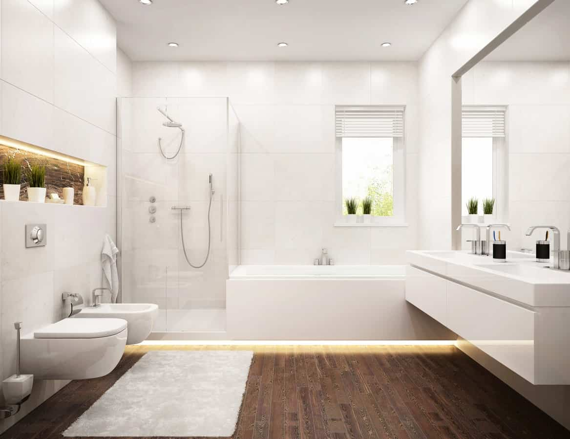 The hardwood flooring of this bright bathroom contrasts the the smooth and sleek floating vanity that matches with the bathtub and toilet beside the shower area that has a glass door. This bathroom has a unique lighting on the bottom of the bathtub and shower.
