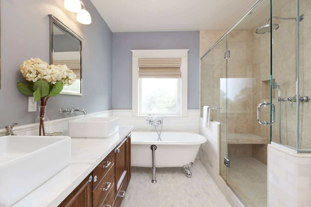 The white freestanding bathtub that has silvery legs is placed in a corner of the bathroom beside the glass enclosed beige shower area across from the wooden vanity with white countertop and freestanding pair of sinks.