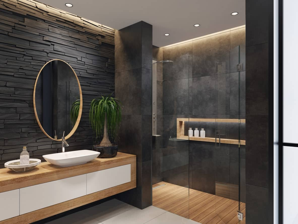 The vanity area of this bathroom has a palette of black textured wall paired with the wooden floating vanity. This is mirrored by the shower area that has a wooden flooring and alcove shelves against the black walls.