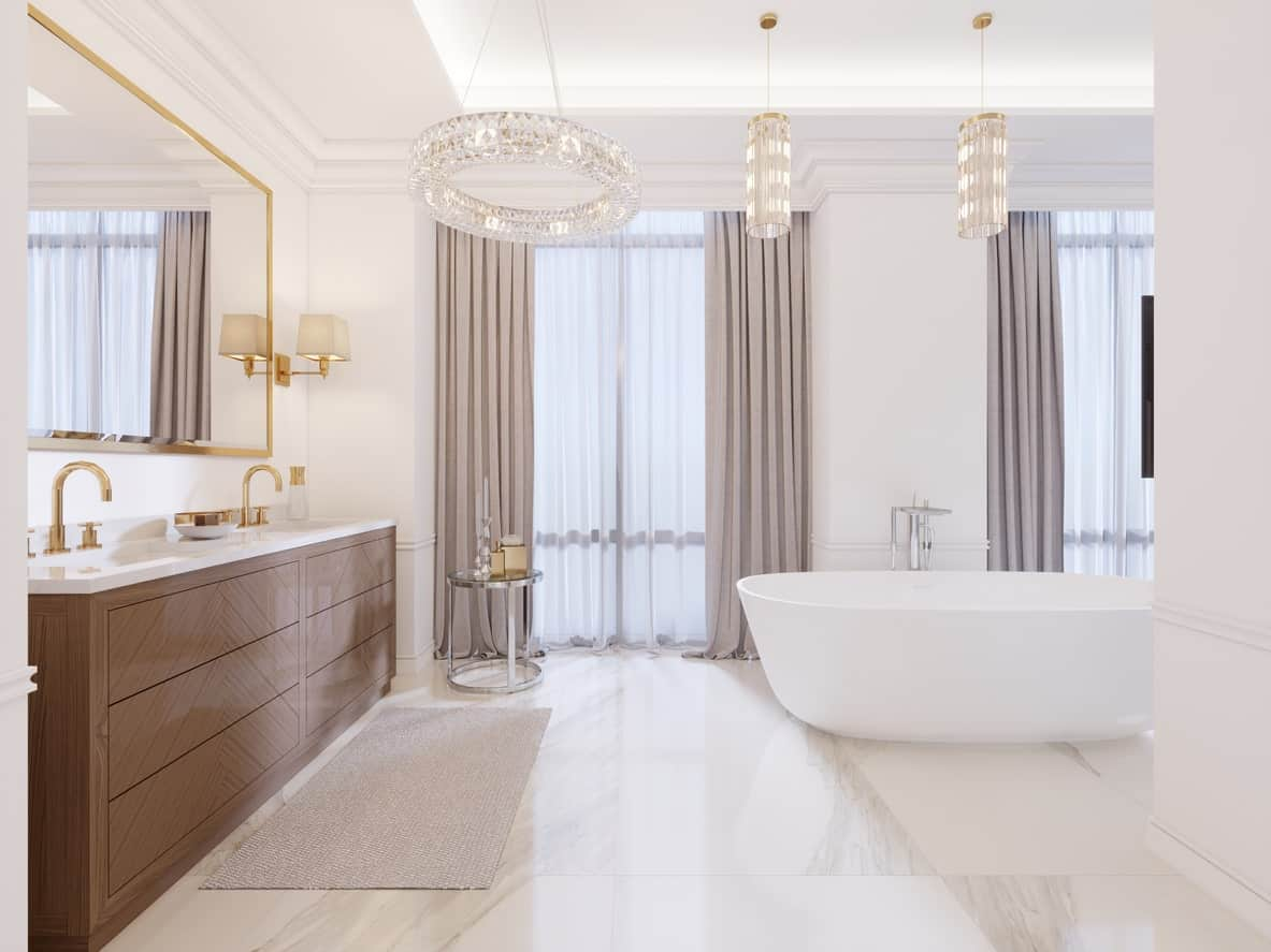 The brightness of the white walls and tray ceiling is augmented by the natural lights coming in from the curtained tall windows flanking the white freestanding bathtub that blends in with the white marble flooring and walls.