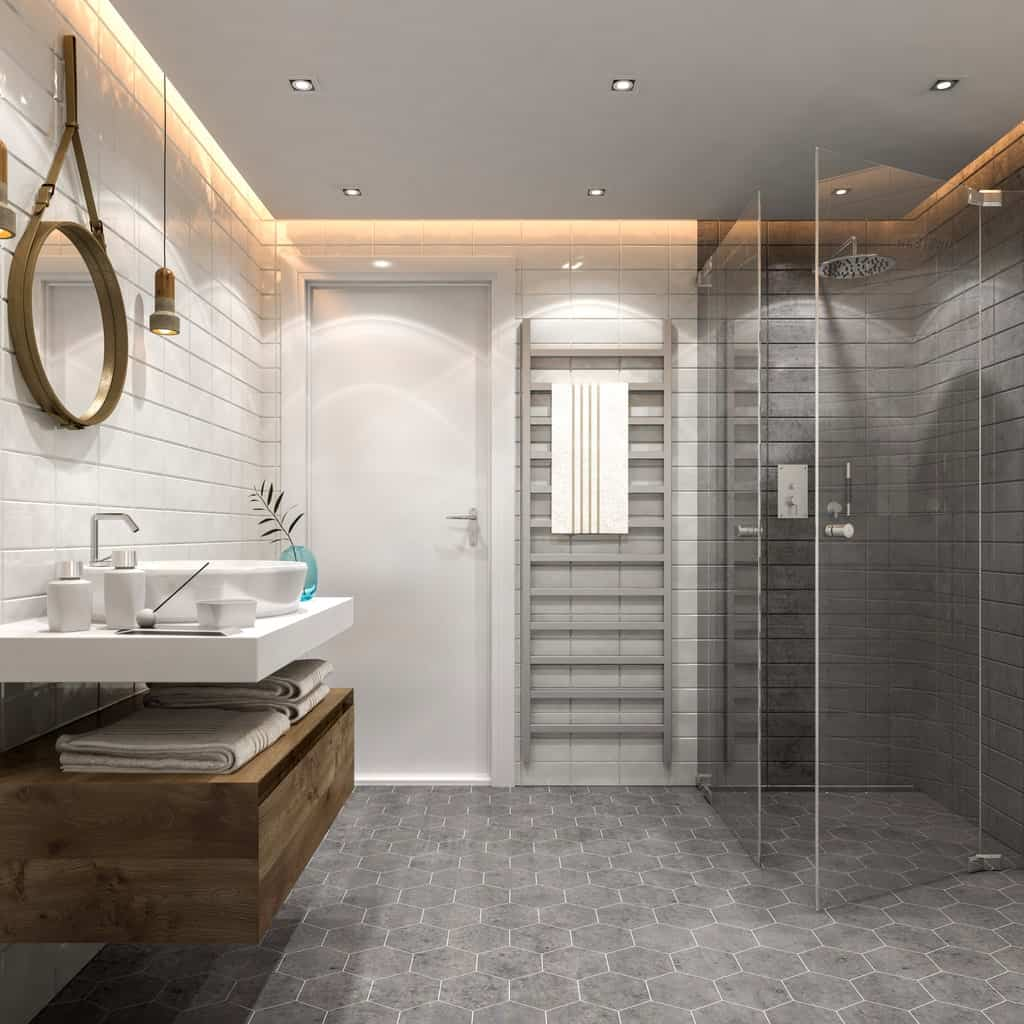 This is a simple bathroom that comforts you with its gray hexagonal floor tiles and the two tones of the wall finish. White for the vanity area that has a rustic mirror and pendant lights while the shower area has dark-toned walls.