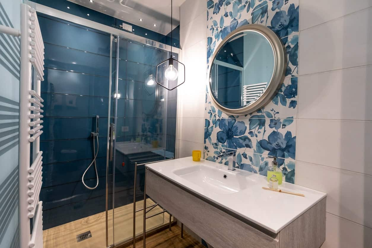 The circular vanity mirror above the white sink is accented with a blue floral portion of the white wall beside the glass -enclosed shower area that has sleek deep green wall finish illuminated by the pendant light of the vanity area.