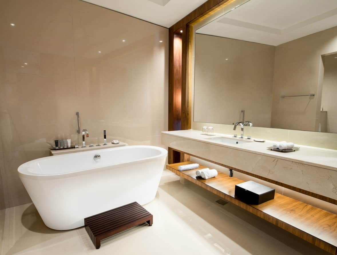 The wall by the freestanding bathtub has a sleek beige tile finish that is complemented by the wooden structure framing the vanity area that has a large mirror mounted over the white marble countertop with a wooden shelf beneath it.