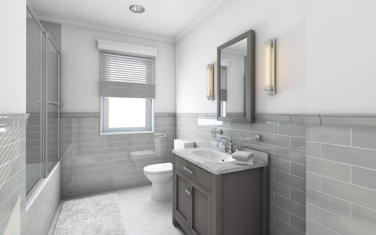 The lower half of the walls of this lovely bathroom is filled with gray tiles arranged in a brick wall pattern that is complemented by the dark gray vanity that has a white marble countertop and silver faucet paired with a wall-mounted mirror with gray frame.