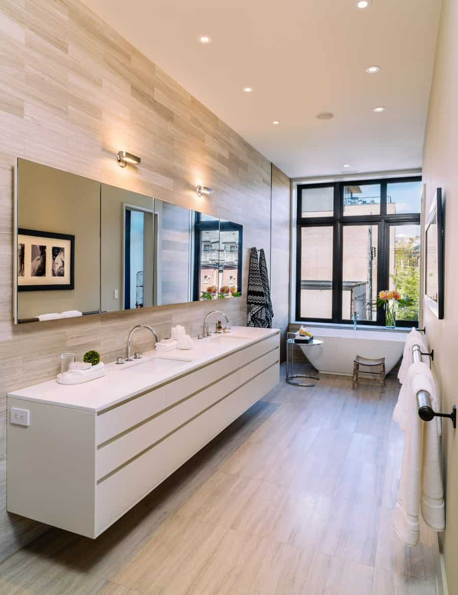 The freestanding white bathtub is placed at the far end of this bathroom by the tall windows with black frames contrasting the white ceiling and floating vanity with two sinks against a wooden wall that matches the floor.