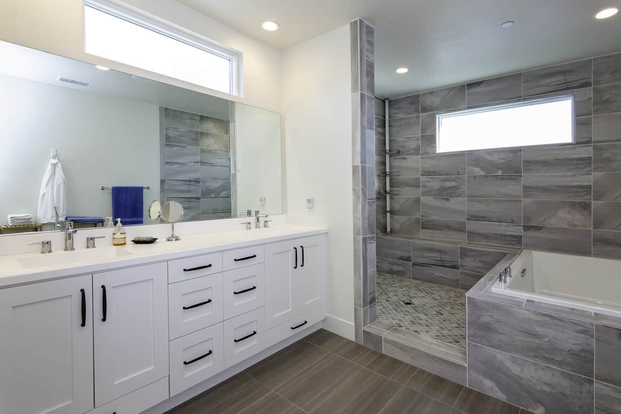 This primary bathroom has two portions. The first portion is the vanity area that has white cabinets and drawers matching the white walls. The second section is the shower and bathtub area that is surrounded by gray tiles on the walls and flooring.