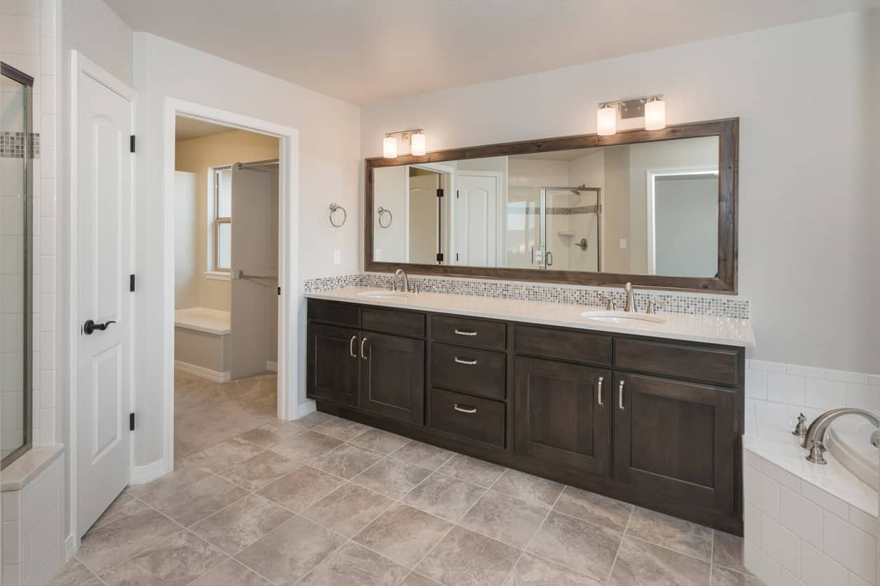 The long vanity mirror is framed with wood that is a nice match with the wooden cabinets and drawers of the vanity that has a white countertop pairing with the tiles of the bathtub and shower area that is complemented by a beige marble flooring.