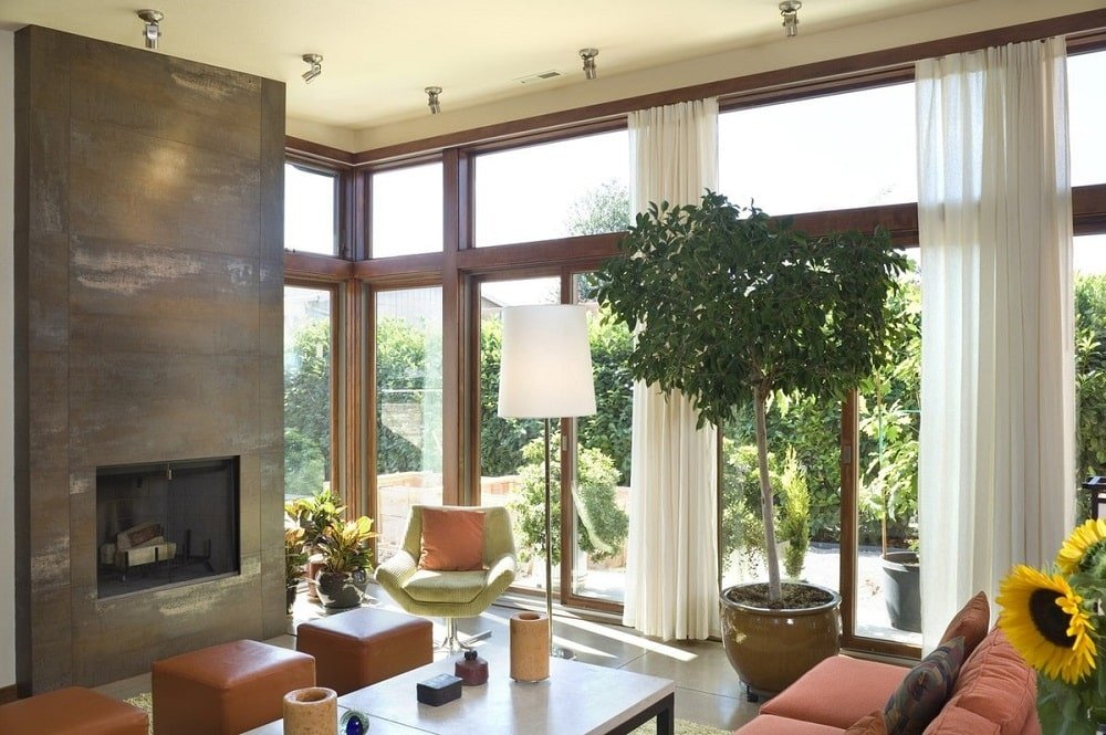 This is a bright living room with glass walls on one side, a large modern fireplace with gray marble structure and a sofa set paired with a large coffee table.