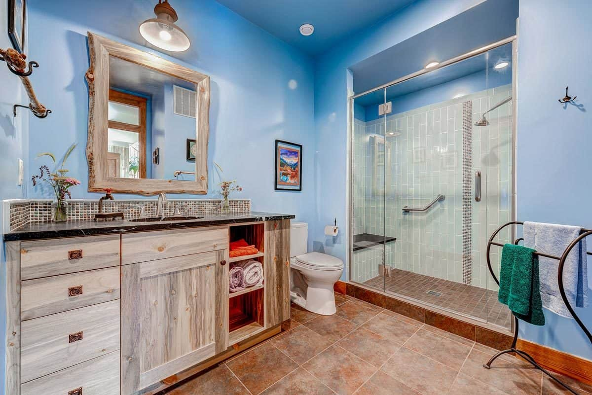 The gorgeous pastel blue tone of the bathroom walls give a nice complement to the earthy tones of the wooden vanity and flooring that contrasts the white toilet and glass wall of the shower area on the far side.
