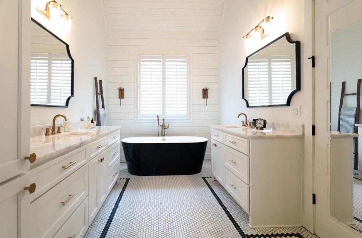 Black framed mirrors along with a freestanding tub add a stunning contrast to the white walls and vanities of this primary bedroom.