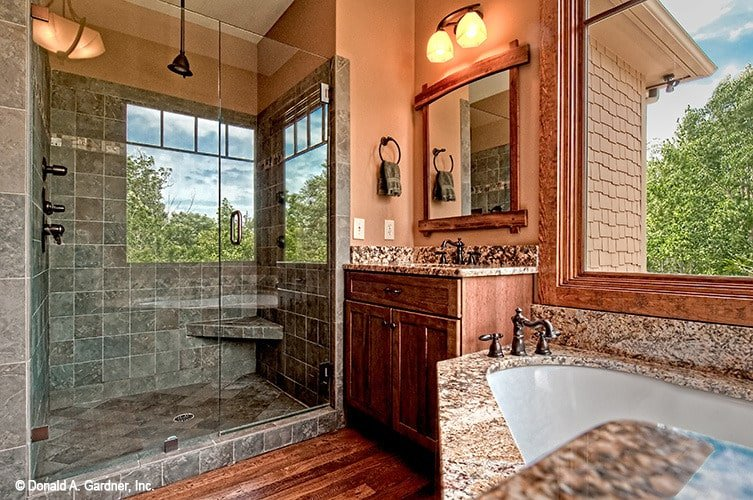 Brown walls complemented with wooden vanity and granite tiles bring a cozy feel to this primary bathroom.