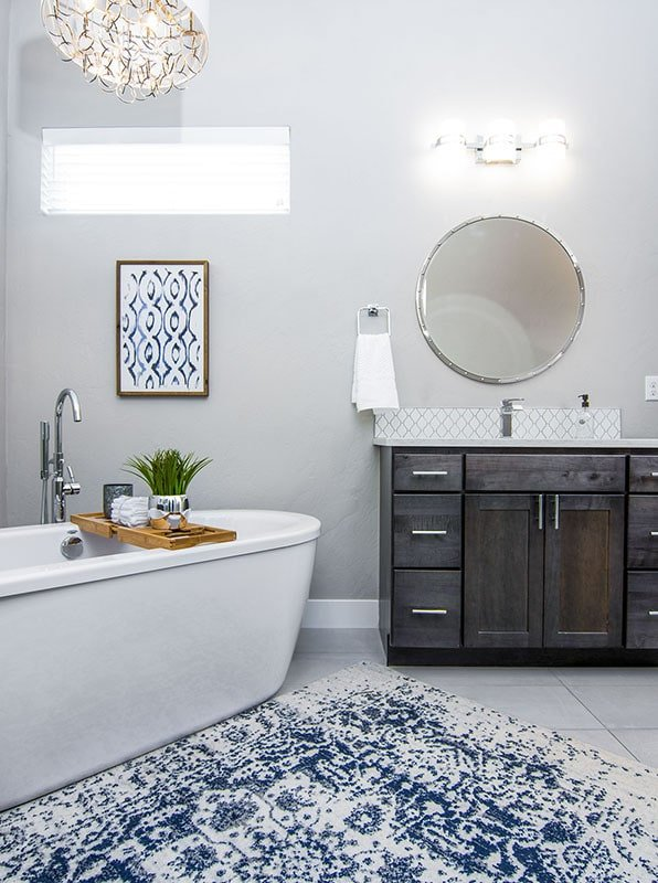 This primary bathroom features lots of interesting elements including a rustic vanity, a stunning drum pendant, and a large distressed rug that matches the framed artwork.