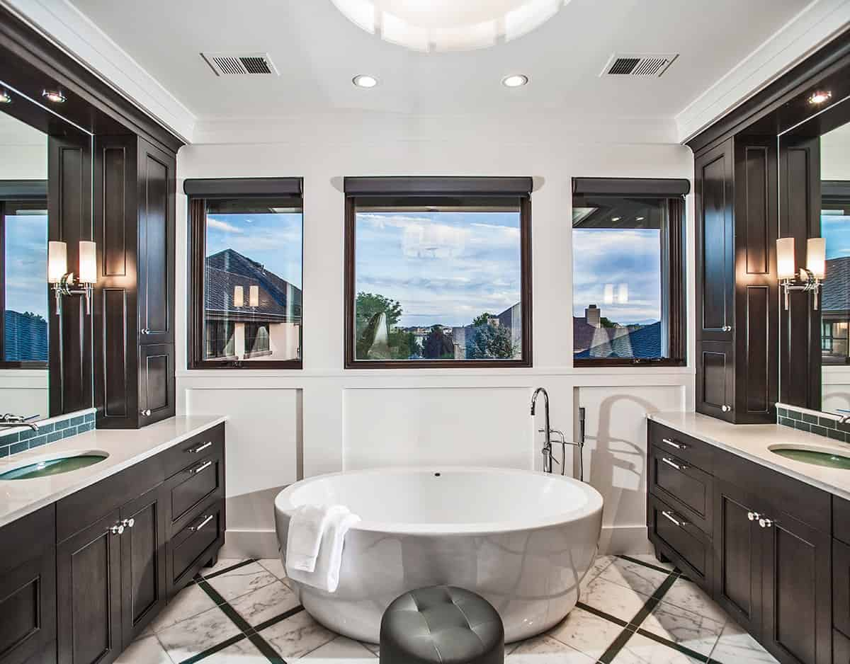 Dark wood vanities set a stunning contrast to the white walls and marble tile flooring of this primary bathroom. The freestanding tub placed under the windows creates a nice focal point to the room.