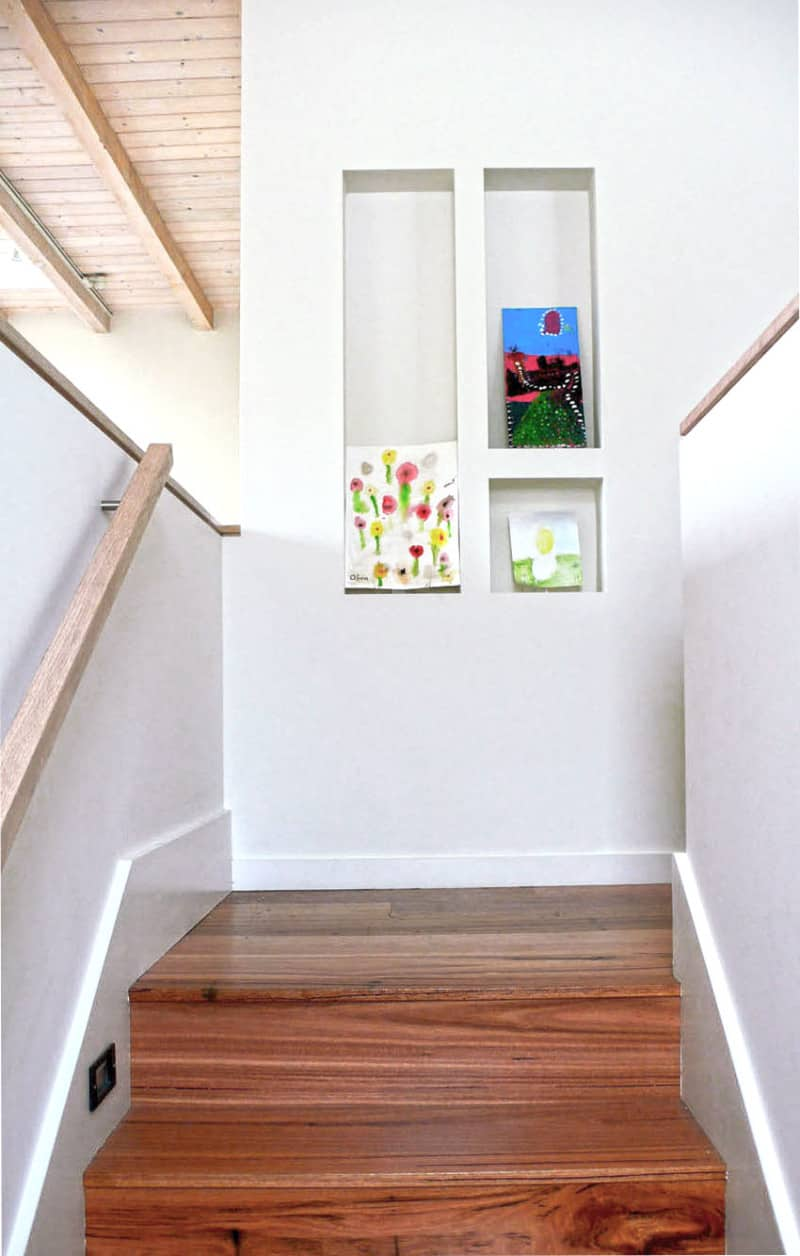 Narrow landing with with wood steps and handrail and an immersed concrete shelves for display.
