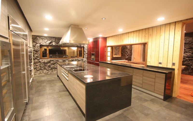 Large U-shaped kitchen featuring a large center island with granite countertop set on the tiles flooring. The lighting makes the kitchen look so glamorous.