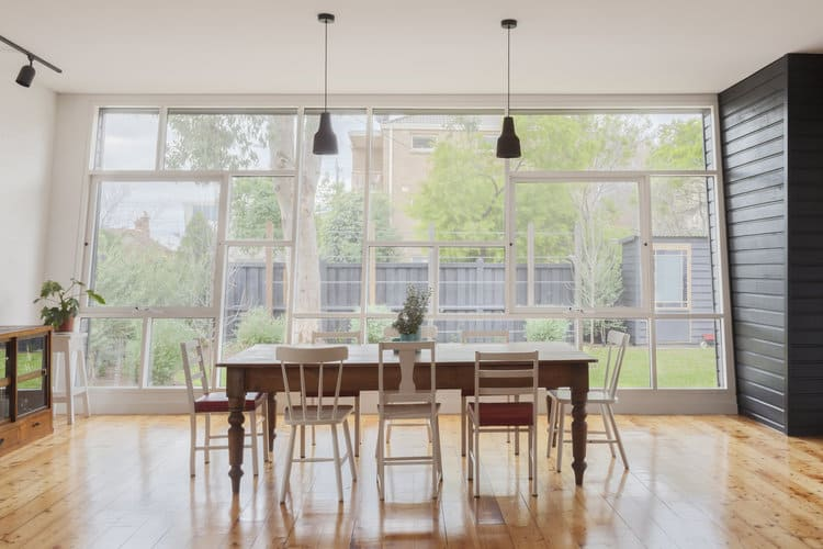 An abundance of natural light flows in through the full height glazing in this dining room with black dome pendants and a wooden dining table surrounded by mismatched chairs over wide plank flooring.