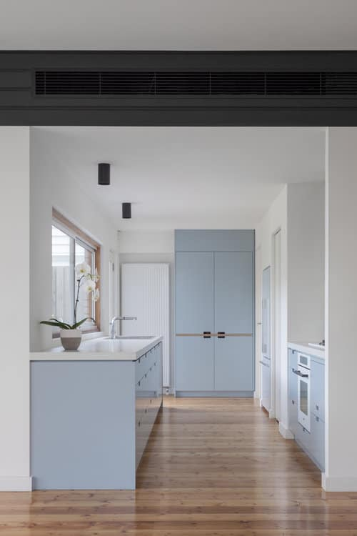 Charming kitchen boasts a white oven and light blue cupboards with pearl white countertop. It has wood plank flooring and glass windows bringing natural light in.