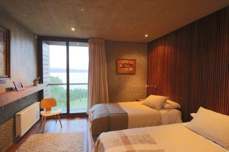Cozy guest bedroom for two with full height windows and wood paneled ceiling fitted with recessed lighting.