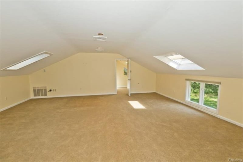 An empty attic room with cream walls, white ceiling, carpeted floor and casement window.
