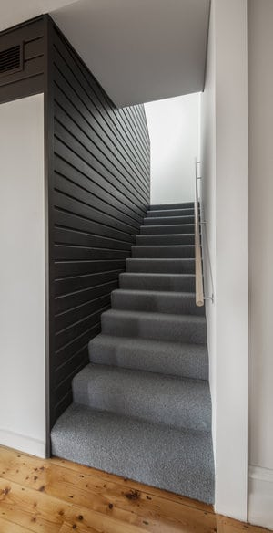 This home boasts a stylish straight staircase with gray carpet floors and a black wall.